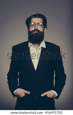 Handsome man bearded hipster male wears vintage glasses black suit with hands in pockets on grey wall - stock photo