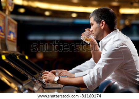 handsome man beeing concentrated in playing the slot machine - stock photo