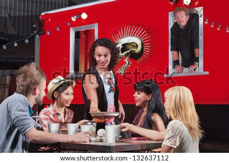 Handsome man bringing plate of food to group of diners at food truck - stock photo