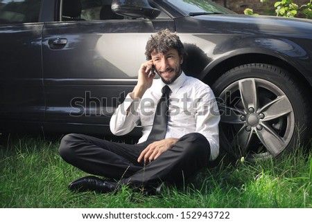 handsome man calls leaning against his car sitting on the grass - stock photo