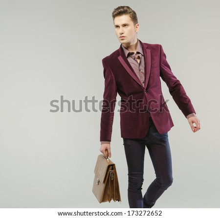 Handsome man carrying a handbag - stock photo