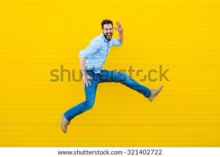 handsome man casual dressed celebrating and jumping on yellow background - stock photo