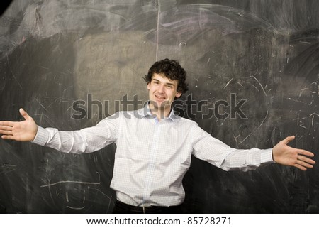 Handsome man casually leaning against the blackboard