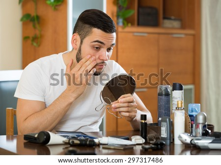 Handsome man checking his eyelid in a mirror - stock photo