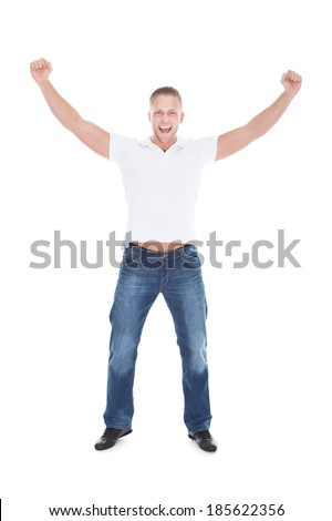 Handsome man cheering in exultation punching the air with his fists as he celebrates good news  full length isolated on white - stock photo