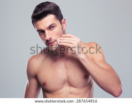 Handsome man cleaning face skin with batting cotton pads over gray background and looking at camera - stock photo