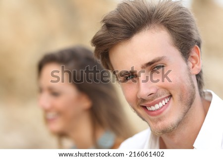 Handsome man close up portrait with a perfect white tooth and smile with a girl in the background - stock photo