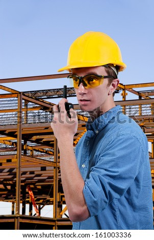 Handsome man construction worker talking on a walkie talkie
