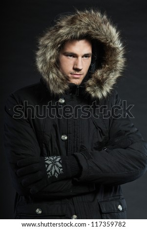 Handsome man dark winter fashion. Studio shot. Wearing black hood jacket and gloves.