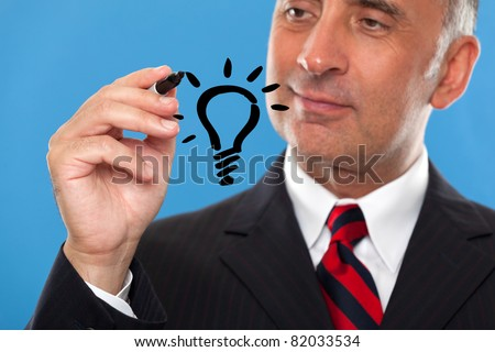 Handsome man drawing a light bulb - stock photo