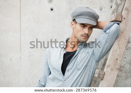 Handsome man dressed in a blue jeans shirt, jeans and a cap, posing - stock photo