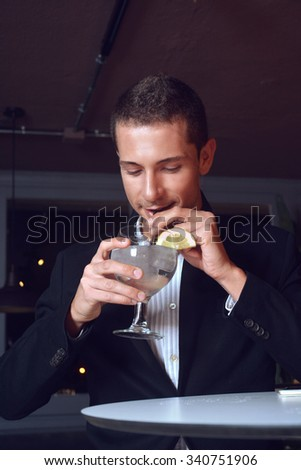 handsome man drinking a gin and tonic cocktail in a stylish bar - stock photo