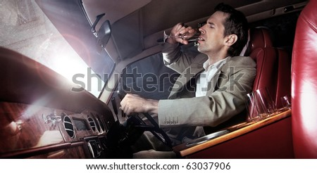 Handsome man drinking in the car - stock photo