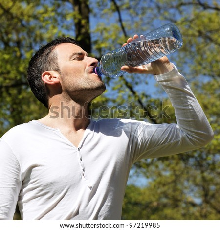 handsome man drinking water in a park - stock photo