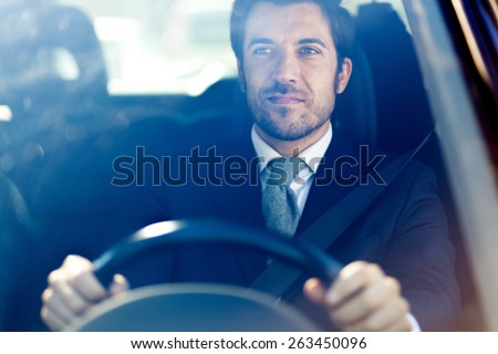 Handsome man driving his car - stock photo