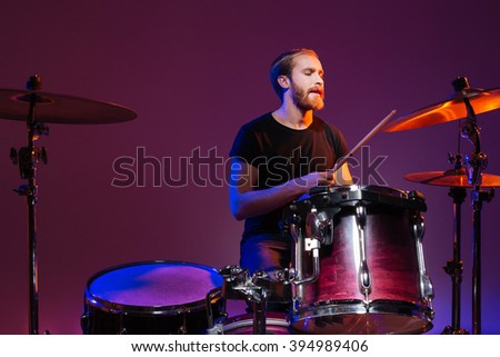 Handsome man drummer sitting and playing on his kit over dark background - stock photo