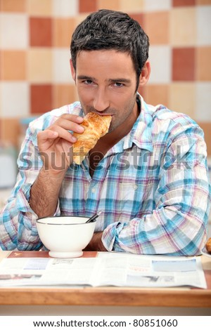 Handsome man eating a croissant - stock photo