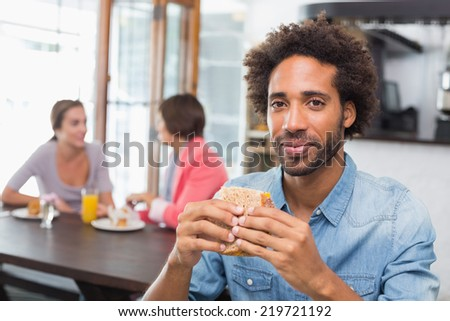 Handsome man eating a sandwich at the coffee shop - stock photo