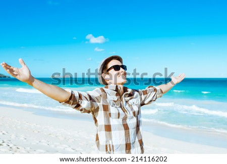 Handsome man enjoying beautiful day at the beach. - stock photo