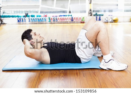 Handsome man exercising abdominal muscles at the gym