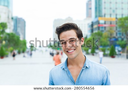 Handsome man face smile outdoor city street, Young attractive businessman casual blue shirt - stock photo