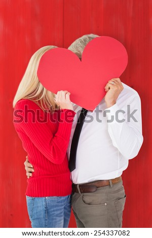 Handsome man getting a heart card form wife against red wooden planks - stock photo