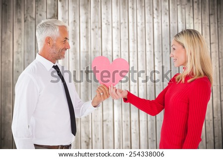 Handsome man getting a heart card form wife against wooden planks background - stock photo