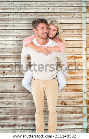 Handsome man giving piggy back to his girlfriend against faded pine wooden planks - stock photo