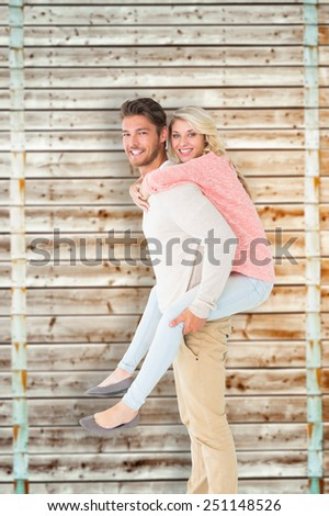 Handsome man giving piggy back to his girlfriend against wooden background in pale wood - stock photo