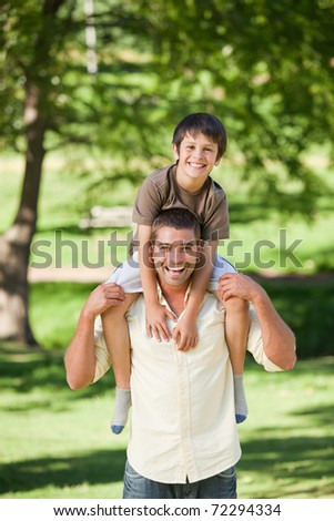 Handsome man giving son a piggyback - stock photo