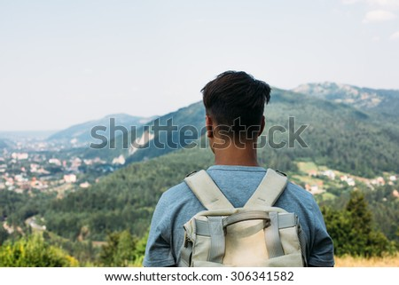 handsome man guy tourist standing alone by the mountain forest landscape during his summer vacation with his backpack back view