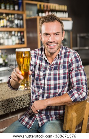 Handsome man having a beer in a pub - stock photo