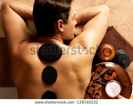 Handsome man having stone massage in spa salon. Healthy lifestyle. - stock photo