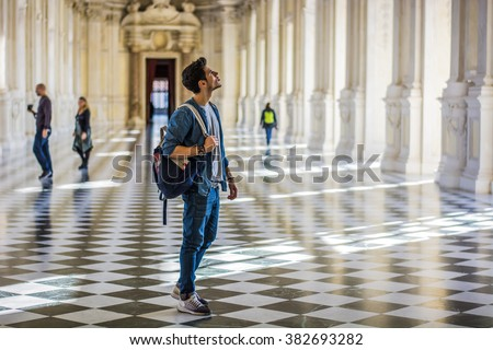 Handsome Man Holding a Guide Inside a Museum - stock photo