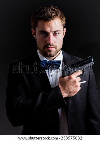 Handsome man holding a gun against black background - stock photo