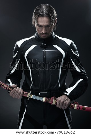 Handsome man holding a samurai sword - stock photo