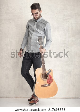 handsome man holding an acoustic guitar against grunge wall - stock photo