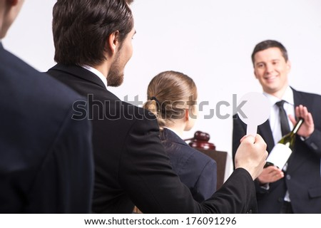 handsome man holding bottle of wine. person selling expensive drinks at auction - stock photo