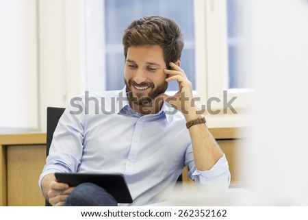 Handsome man holding digital tablet in office - stock photo
