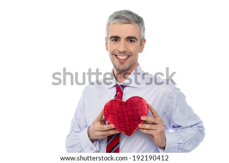 Handsome man holding heart shaped gift box - stock photo