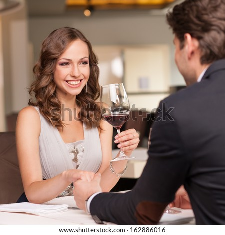 Handsome man holding his girlfriend hand. Drinking wine and smiling  - stock photo
