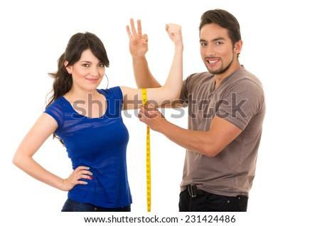 handsome man holding measuring tape around thin fit young girl's arm isolated on white - stock photo