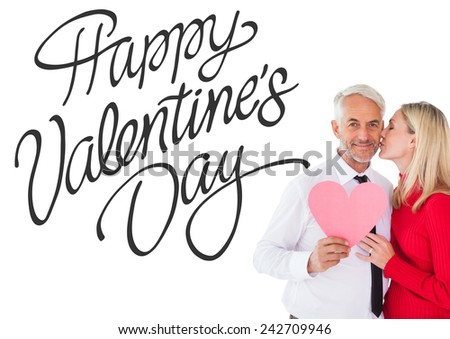 Handsome man holding paper heart getting a kiss from wife against happy valentines day - stock photo