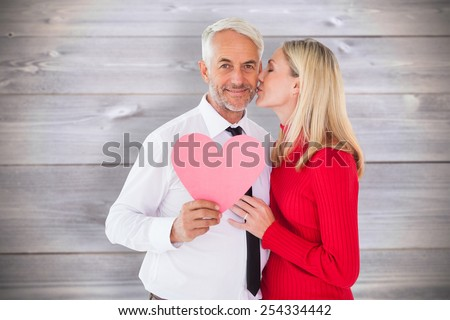 Handsome man holding paper heart getting a kiss from wife against wooden planks background - stock photo