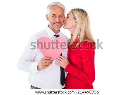Handsome man holding paper heart getting a kiss from wife on white background - stock photo
