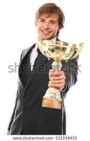 Handsome man in a suit with prize cup over a white background - stock photo