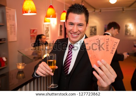 Handsome man in a theater, concert or cinema presenting tickets - stock photo