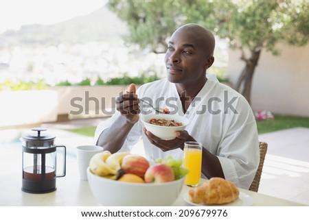 Handsome man in bathrobe having breakfast outside on a sunny day - stock photo