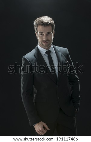 handsome man in black suit on a black background - stock photo