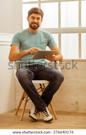 Handsome man in casual clothes using a tablet, looking in camera and smiling while sitting on a chair near the window - stock photo